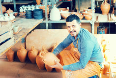 Man potter holding ceramic vessels in atelier Royalty Free Stock Photo