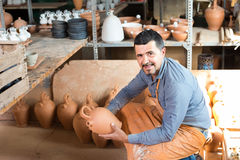 Man potter holding ceramic vessels in atelier Stock Photos