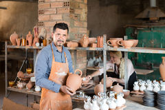 Man potter holding ceramic vessels in atelier Stock Photography