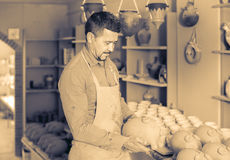 Man potter holding ceramic vessels in atelier Royalty Free Stock Photos