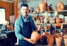 Man potter holding ceramic vessels in atelier Stock Image