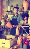 Man potter holding ceramic vessels in atelier. Spanish man potter holding ceramic vessels in atelier stock photo