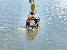 Man pouches motorbike through water. During the worst flooding in decades on October 21, 2011 Rongsit Road, Phathumtrani, Thailand Royalty Free Stock Images
