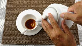 Man pour hot black coffee into a white coffee cup.