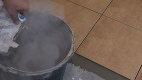 Man pour special tile glue mixture to bucket. Closeup shot stock video