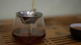 Man pour tea into the chahai through a sieve. Chinese tea ceremony stock footage