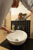 Man poured a bottle of vodka down the sink. Addicted man poured a bottle of vodka down the sink in the bathroom Royalty Free Stock Photos
