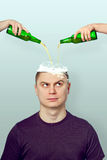 Man poured the liquid in the head. Man in the head is poured the liquid from the bottle with two hands Stock Photography
