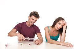 Man pouring alcohol and woman sitting upset at table. Photo of women with alcoholic husband on white background stock image