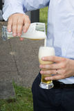 Man pouring beer in a glass outside at summer Stock Photography