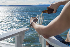 Man pouring beer into mug on seaside deck. Man sitting outside on a seaside deck pouring a freshly opened beer into a frosty mug royalty free stock photo