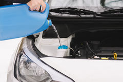 Man pouring car winter windshield washer fluid Stock Photo