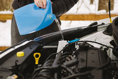Man pouring car winter windshield washer fluid Stock Images