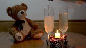 Man pouring champagne into glass , on wooden table. With teddy bear behind stock footage