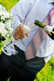 Man pouring champange to wineglass. Man with necktie pouring champange to wineglass. Wedding bouquet in the left Royalty Free Stock Images