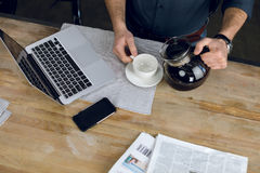 Man pouring coffee in cup on desk with laptop and newspapers Stock Image