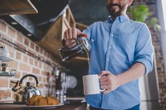 Man pouring coffee into the cup. Low angle view of happy man pouring coffee into the cup at morning in the kitchen Stock Images