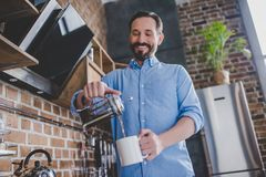 Man pouring coffee into the cup. Low angle view of happy man pouring coffee into the cup at morning in the kitchen Royalty Free Stock Photos