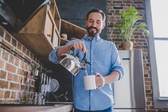 Man pouring coffee into the cup. Low angle view of happy man pouring coffee into the cup at morning in the kitchen Stock Image