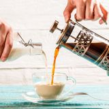 Pouring coffee and milk into a cup Stock Photography