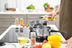 Man pouring cooking oil from bottle into saucepan. On stove royalty free stock image