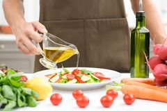 Man pouring cooking oil onto vegetable salad. In kitchen stock images