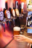 Man pouring craft beer from beer taps in frozen glass with froth. Selective focus. Alcohol concept. Vintage style. Beer craft. royalty free stock photo