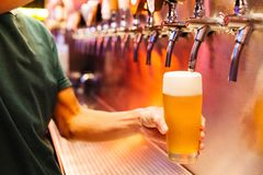 Man pouring craft beer from beer taps in frozen glass with froth. Selective focus. Alcohol concept. Vintage style. Beer craft. Bar table. Steel taps. Shiny stock photos
