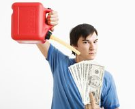 Man pouring gas on money. Asian young man holding gas can pouring gasoline onto money Stock Photography
