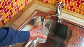 Man pouring a glass of fresh water from a kitchen faucet stock footage