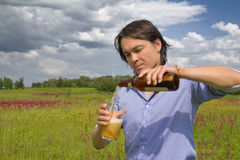 Man pouring himself a beer on a spring meadow Royalty Free Stock Photos
