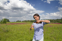 Man pouring himself a beer on a spring meadow Stock Photography