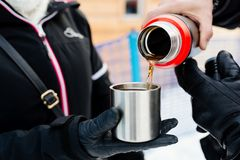 Man pouring hot tea from a thermos. Into a metal mug Royalty Free Stock Image