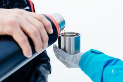 Man pouring hot tea from a thermos. Into a metal mug Stock Photo