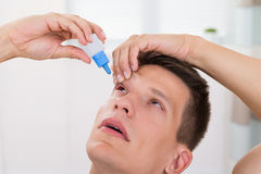 Man Pouring Medicine Drops In His Eyes Stock Images