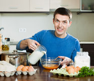Man pouring milk in bowl Stock Photos
