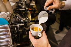Man Pouring Milk into Coffee Making Espresso. Some milk added into milled ground coffee beans. Barman prepares hot strong beverage holding cups in hands at the Stock Image