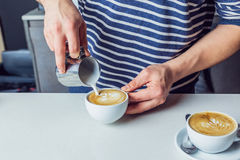 Man pouring milk into coffee. Partial close up view of man pouring milk into coffee Royalty Free Stock Photography
