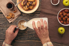 Man pouring milk into a cup of aromatic black coffee Stock Photo