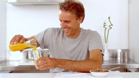 Man pouring orange juice in his glass Stock Image