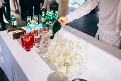Man, pouring out champagne in glasses on a table royalty free stock photography