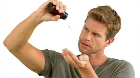 Man pouring out pills on white background Royalty Free Stock Photography