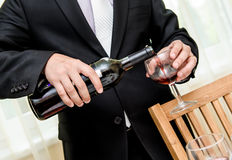 Man pouring red wine from bottle into a glass Stock Photos