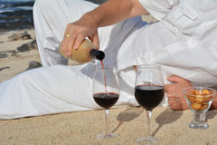 Man pouring red wine from bottle into a glass on the beach Royalty Free Stock Image
