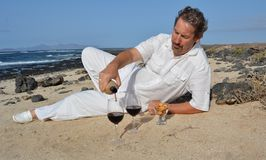 Man pouring red wine from bottle into a glass on the beach Stock Photo
