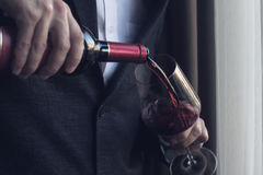 Man pouring red wine into a glass Stock Photo