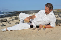 Man pouring red wine into two glasses on beach Royalty Free Stock Image