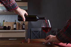 Man pouring red wine into a wineglass Royalty Free Stock Photos