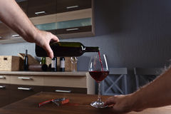 Man pouring red wine into a wineglass Stock Photos