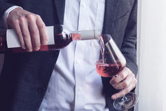 Man pouring rose wine into a glass Royalty Free Stock Photo